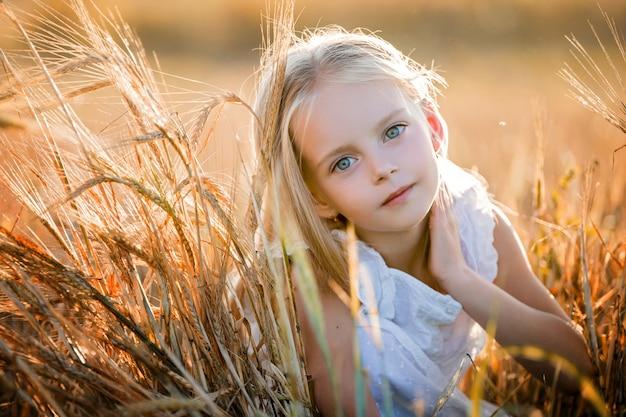 Portret dziewczynki z długimi blond włosami w białej sukni siedzącej wśród uszu dojrzałej pszenicy na polu