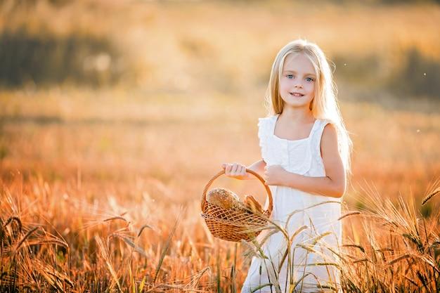 Portret dziewczynki z długimi blond włosami w białej sukni stojącej na polu wśród kłosów pszenicy