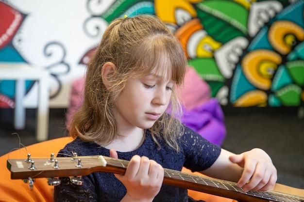 Portret dziewczynki z gitarą akustyczną w dłoniach