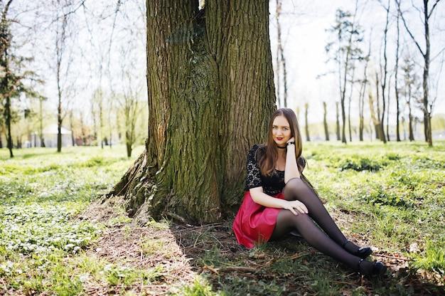 Portret dziewczynki z jasnym makijażem z czerwonymi ustami, czarnym naszyjnikiem na szyi i czerwonej skórzanej spódnicy siedzącej przy drzewie w parku.