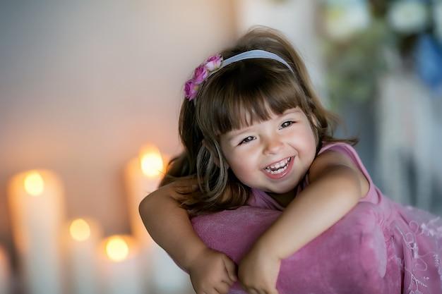 Portret dziewczynki z językiem wiszącym na światłach tlącej się świecy.