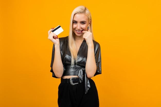 Portret dziewczynki z kartą z makiety na zakupy na żółtej ścianie