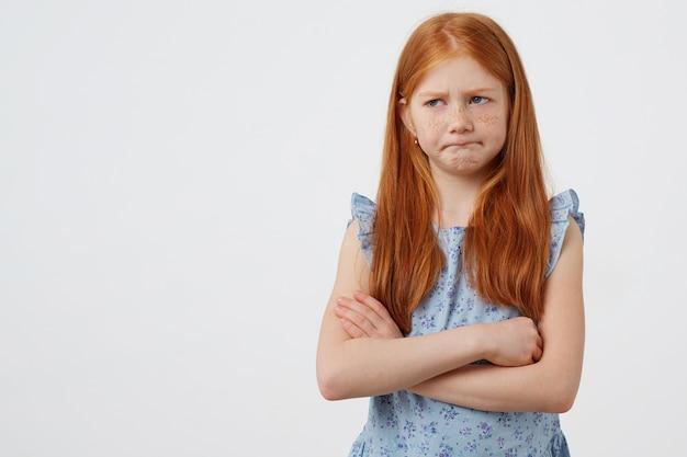 Portret dziewczynki z małymi obrażonymi piegami rudowłosa dziewczyna z dwoma ogonami, malkontent wygląda dziwnie, nosi niebieską sukienkę, stoi ze skrzyżowanymi rękami na białym tle.
