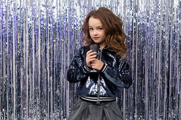 Portret dziewczynki z mikrofonem na błyszczącą ścianę
