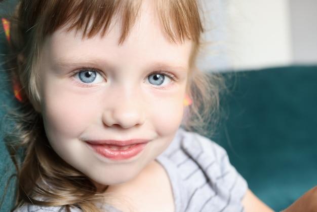 Portret dziewczynki z niebieskimi oczami i lekkim uśmiechem