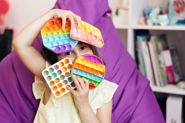 Portret dziewczynki z nowoczesną zabawką popit kolorową i jasną zabawką pop it prosty dołek