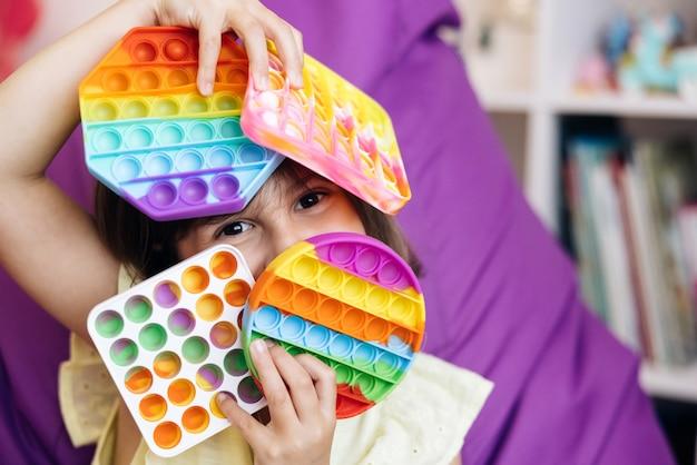 Portret dziewczynki z nowoczesną zabawką popit modna antystresowa zabawka sensoryczna fidget push pop it