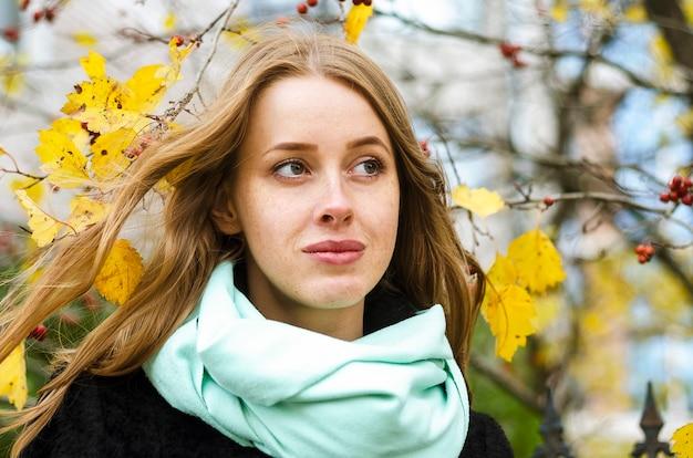 Portret dziewczynki z piegami i długie rude, imbirowe włosy na tle jesieni