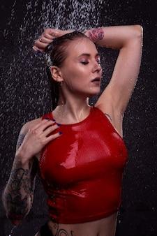 Portret dziewczynki z pięknymi piersiami w mokrej czerwonej koszulce pod prysznicem z jasnymi kroplami spadającej wody.