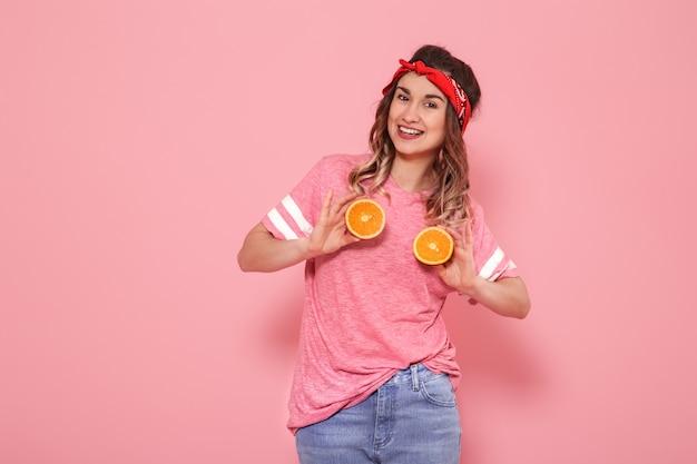 Portret dziewczynki z pomarańczami w ręku, na różowej ścianie