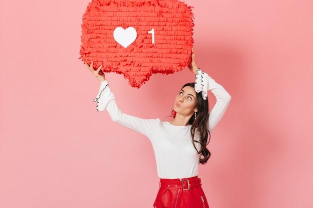 """Portret dziewczynki z zaciekawieniem patrzącej na ogromny znak """"lajka"""" z instagrama. brunetka w czerwonej spódnicy pozowanie na różowym tle."""