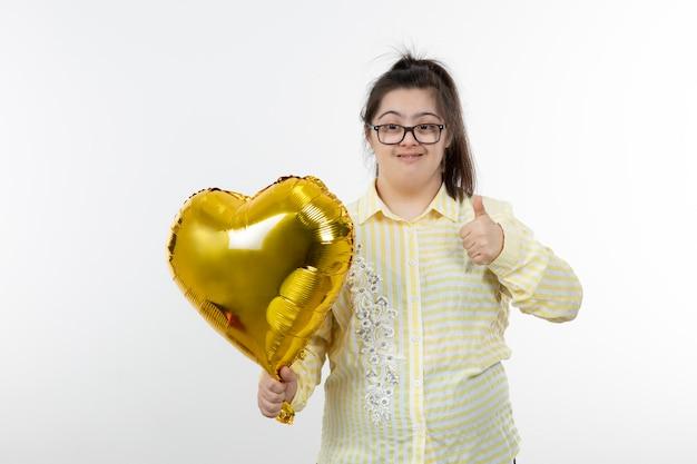 Portret dziewczynki z zespołem downa z balonem pokazując kciuk do góry