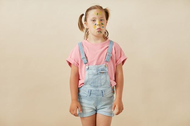 Portret dziewczynki z zespołem downa z pomalowaną twarzą pozuje do kamery na białym tle