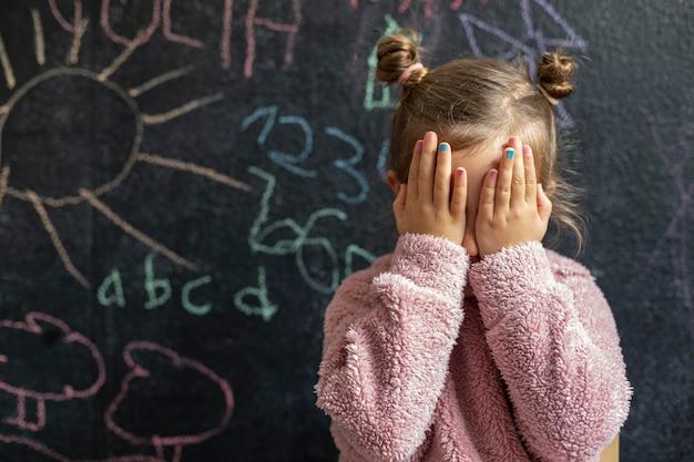 Portret dziewczynki zdenerwowany zakrywający twarz