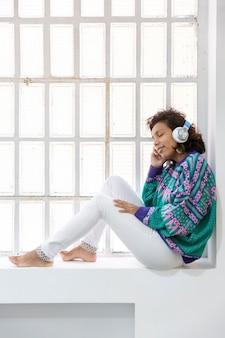 Portret dziewczyny brunetka, słuchanie muzyki, siedząc na oknie. miejsce na tekst.