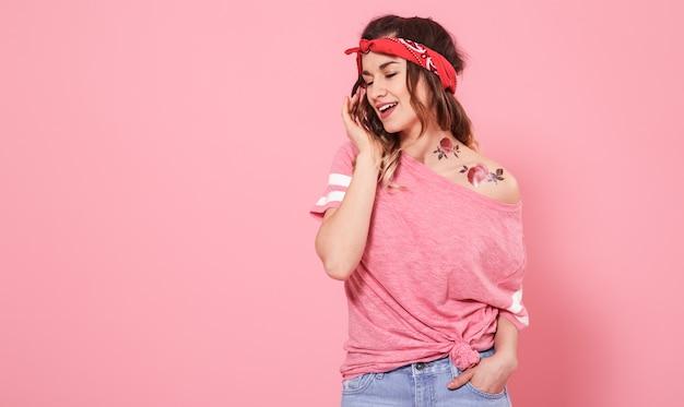 Portret dziewczyny hipster z tatuażem, na różowym tle ściany