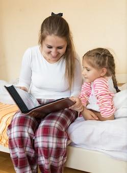 Portret dziewczyny i matki czytających dużą książkę w sypialni