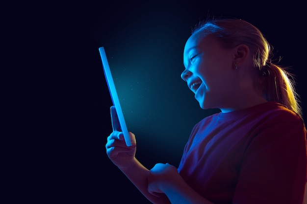 Portret dziewczyny kaukaski na białym tle w ciemnym studio w świetle neonu