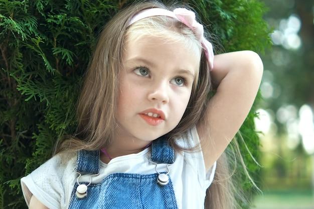 Portret dziewczyny ładne dziecko stojąc na zewnątrz w parku latem.