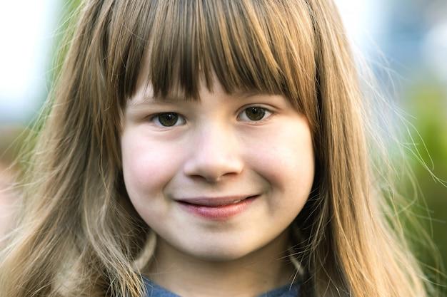 Portret dziewczyny ładne dziecko, szare oczy i długie jasne włosy, uśmiechając się na zewnątrz na niewyraźne zielone jasne tło. słodkie dziecko kobiece na ciepły letni dzień na zewnątrz.