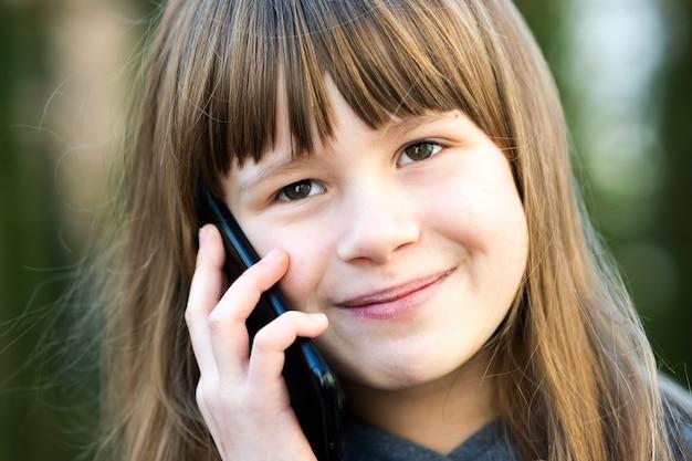 Portret dziewczyny ładne dziecko z długimi włosami, rozmawia przez telefon komórkowy