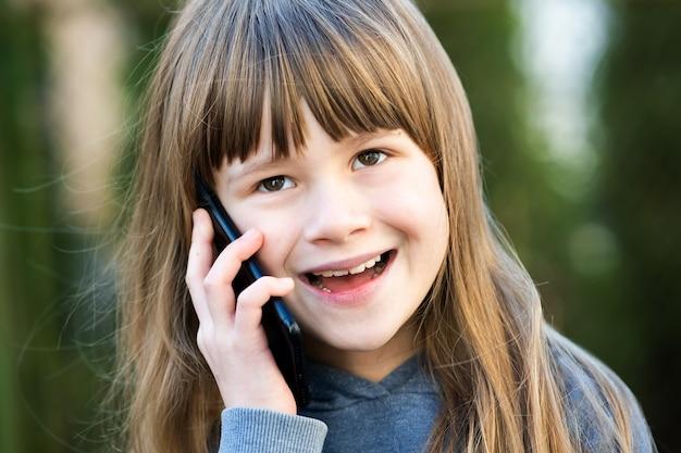 Portret dziewczyny ładne dziecko z długimi włosami rozmawia przez telefon komórkowy.