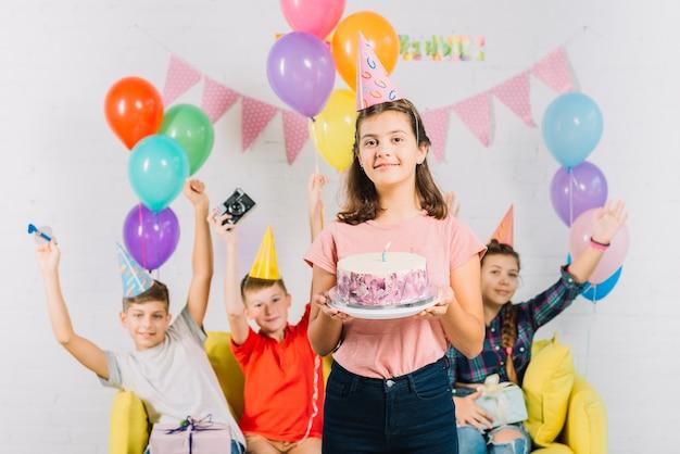 Portret dziewczyny mienia urodzinowy prezent z jej przyjaciółmi siedzi w tle