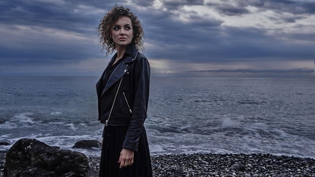 Portret dziewczyny modelka w czarnej kurtce, pozowanie na tle morza