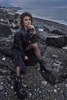 Portret dziewczyny modelka w czarnej kurtce siedzi na kamieniu nad morzem