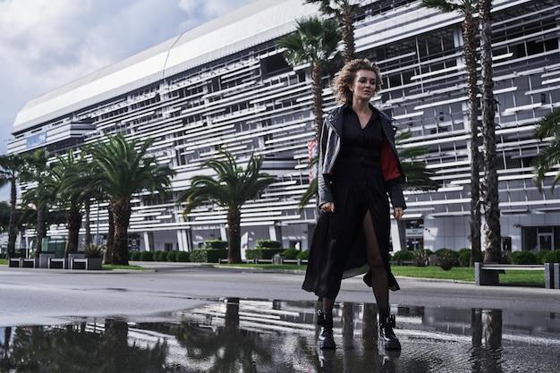 Portret dziewczyny modelka w czarnych ubraniach spacery miejską drogą z palmami