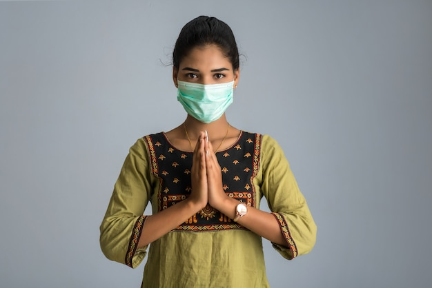 Portret dziewczyny noszenie maski medycznej robi pozdrowienia z namaste gest.