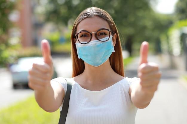 Portret dziewczyny optymistyczne na sobie maskę ochronną pokazując kciuki do góry na ulicy miasta