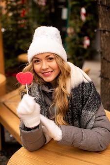 Portret dziewczyny piękna trendu, która trzyma lolipop postać serca.
