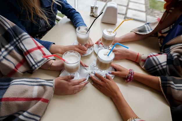 Portret dziewczyny piją kawę w kawiarni z bliska. szklanka cappuccino ze słomką w rękach kobiety. dziewczyny mówią za filiżankę kawy. przyjaciele kobiety rozmawiają i trzymają filiżanki kawy w restauracji