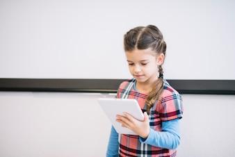 Portret dziewczyny pozycja przeciw ścianie używać cyfrową pastylkę