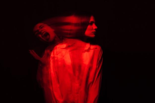 Portret dziewczyny-psychiki ze schizofrenią i zaburzeniami psychicznymi w białej koszuli na czarnym tle