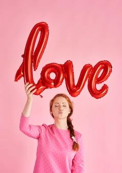 Portret dziewczyny puszczającej buziaka i trzymającej balon