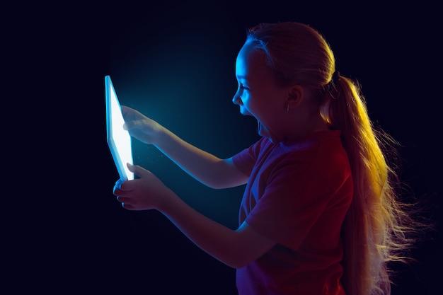 Portret dziewczyny rasy kaukaskiej na ciemnym tle studyjnym w świetle neonowym