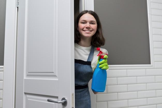Portret dziewczyny robi sprzątanie w łazience. nastolatek w rękawiczkach fartuch z detergentem i szmacianą gąbką uśmiecha się patrząc na kamery. sprzątanie, czystość w domu, obsługa, koncepcja młodych ludzi