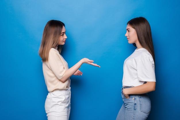 Portret dziewczyny rozmawiają spędzać czas na białym tle na niebieskiej ścianie
