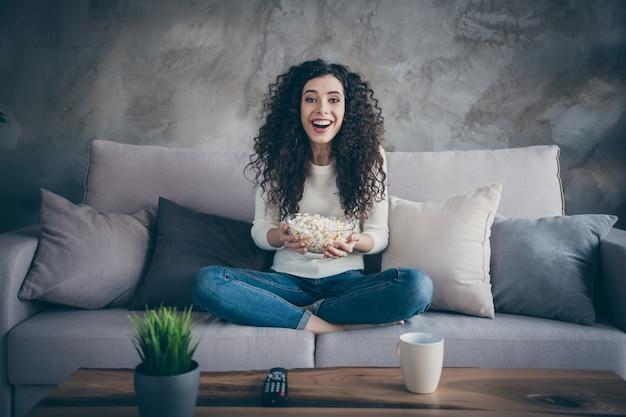 Portret dziewczyny siedzącej na kanapie jedzenie kukurydzy w pokoju w nowoczesnym stylu wnętrza loft przemysłowych