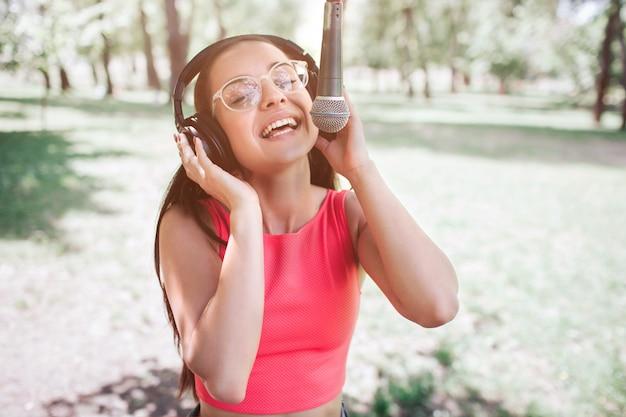 Portret dziewczyny stoi na zewnątrz i śpiewa do mikrofonu. słucha muzyki w tym samym czasie, gdy śpiewa. młoda kobieta cieszy się chwilą.