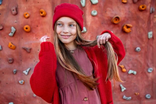 Portret dziewczyny stojącej obok ścian wspinaczkowych
