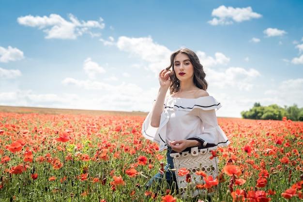 Portret dziewczyny uroda i moda w polu maku. czas letni