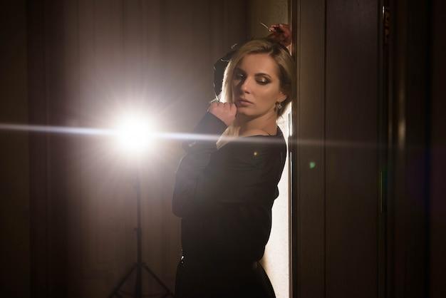 Portret dziewczyny w czarnej sukni pozowanie w podświetlenie