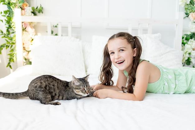 Portret dziewczyny w domu w łóżku z kotem