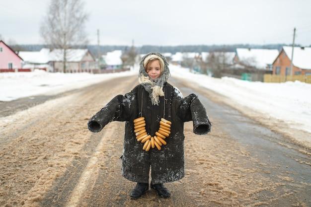 Portret dziewczyny w ponadgabarytowej znoszonej kurtce na sobie bajgle na szyi w zimowy dzień