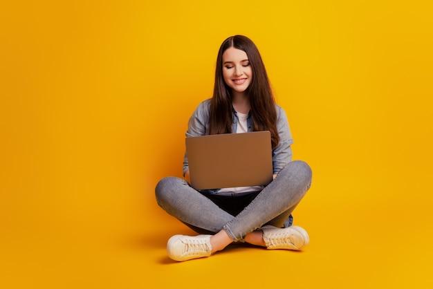 Portret dziewczyny z laptopem siedzi na podłodze ze skrzyżowanymi nogami na żółtym tle