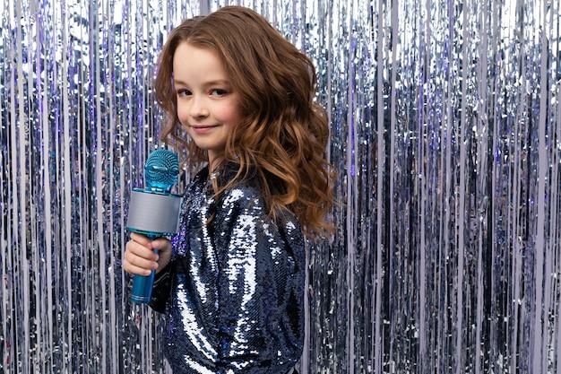 Portret dziewczyny z mikrofonem na błyszczącej ścianie z pustą przestrzenią