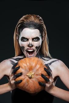 Portret dziewczyny z przestraszonym szkieletowym makijażem trzymającym dynię i krzyczącym na czarnym tle